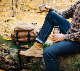 Man resting on fallen tree trunk with thermos.