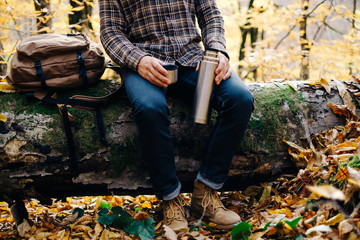 Man sitting on fallen tree trunk with thermos.
