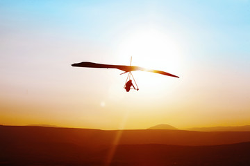 Hang-glider  flight in sky in sunset time over the .Galilean hills, Mevo Hama, Israel Wall mural