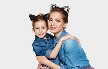 Portrait of mother and daughter posing together wearing funny cat ears. Cheerful ladies in jean jackets on grey background. Happiness and family concept