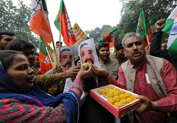 Supporters of India's ruling BJP offer sweets to a man wearing a mask of Indian Air Force pilot Wing Commander Abhinandan Varthaman to celebrate after Abhinandan was released by Pakistan, in New Delhi