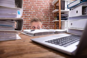 Businessman Hiding Behind The Desk
