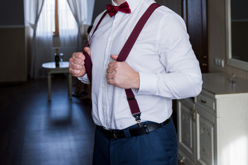 the groom holds his hands suspenders in a suit