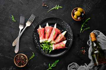 Prosciutto with pear and arugula. Cold snacks. Top view. Free space for your text.