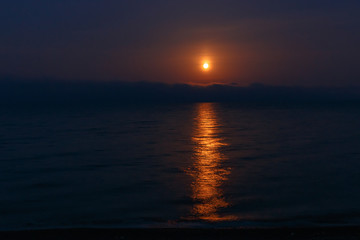 Moon goes down in the sea at the early morning