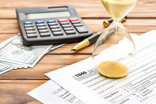 Hourglass with tax form and calculator on the wooden table. Tax time concept.