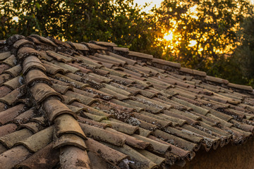 old dirty brown shingle house soft focus roof outdoor in evening sunset time with sun rays background, rural environment