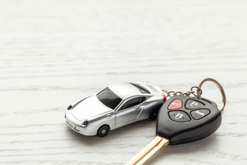 Car keys with remote control security and car key chain on white wooden background. Copy space for text