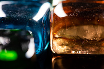 Macro photo of glass cubes of different colors on a black background with reflections