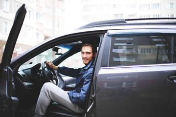 businessman sitting behind the wheel of a car