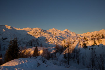 Sunset in snowcaped mountains. Mountains are orange color. Slovenia, Juliana Alps, Komna. The paradise for ski touring.