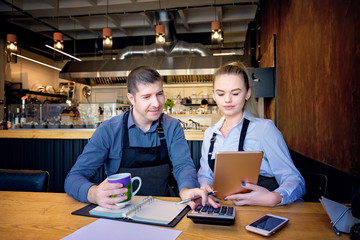 Restaurant employees checking monthly reports. Man and woman wearing apron doing accounts after hours in a small restaurant