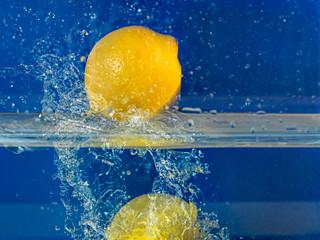 citron jaune dans l'eau avec éclaboussures