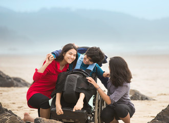 Disabled brother in wheelchair hugging older sisters on beach