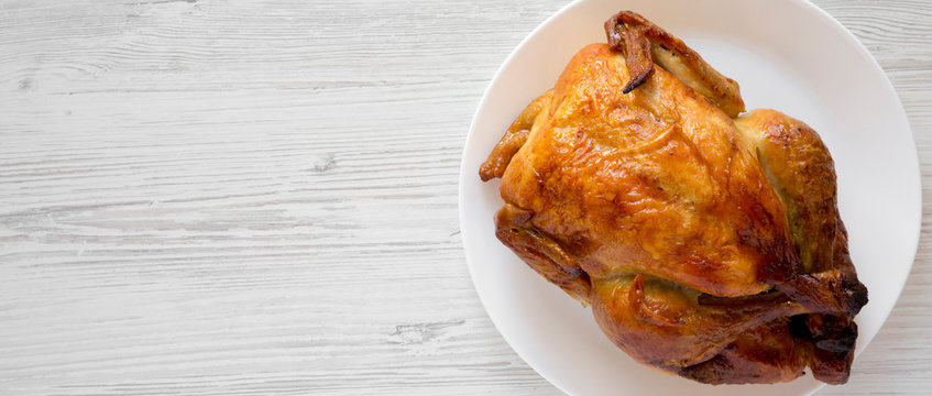 Homemade tasty rotisserie chicken on white plate over white wooden background, top view. Copy space.