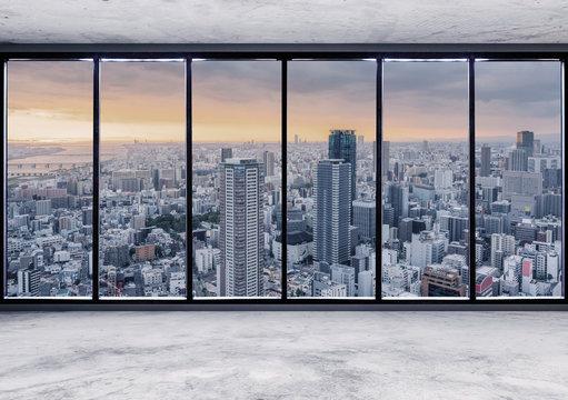 Empty interior space with skyscraper city view in sunrise through window