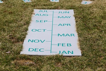 The months of the year written in green on the stone block.