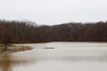 A view of the lake in the park on a cloudy winter day.
