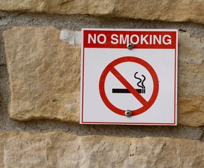 The red and white no smoking sign on the stone wall.