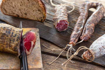 Local wild pork meat , delicatessen, made Corsica France wooden background Wall mural