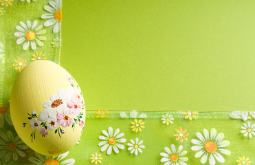 Beautiful painted Easter egg eggs with flowery ribbon and green background and copy space