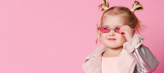 Portrait of a little girl in stylish clothing posing on pink background and playing up