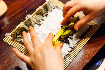 A young women preparing homemade vegan sushi on a wooden table