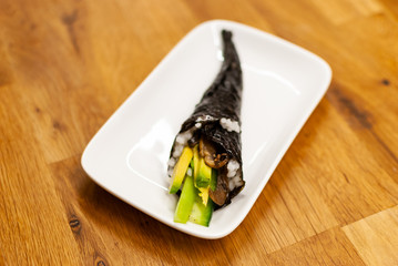 Homemade vegan Temaki-Sushi filled with avocado on a small plate on a wooden table