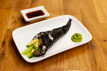 Homemade vegan Temaki-Sushi filled with avocado on a small plate on a wooden table with soy sauce and wasabi
