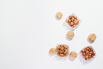 Peanuts, hazelnuts, almonds and walnuts on a white background