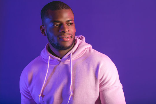 Indoor portrait of afro american guy, dressed in white hooded sweatshirt isolated on purple studio background. Sports and Street Fashion.