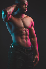 African male athlete with naked torso with six pack posing against dark wall. Low key photo.