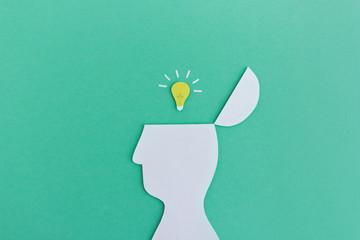 Idee und Inspiration - Kopf Silhouette aus Papier mit Glühbirne-Symbol