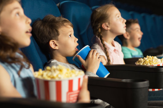 Group of happy kids enjoying a movie at the cinema
