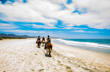Cabo San Lucas, Mexico - 2019. Tourists horseback riding on the beach in Cabo San Lucas, Baja California.