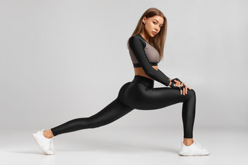 Fitness woman doing lunges exercises for leg muscle workout training. Active girl doing front...