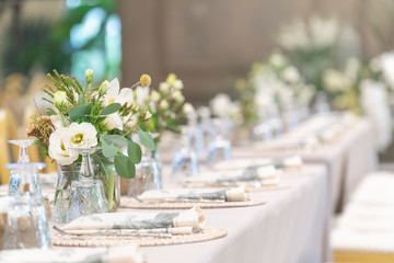 Setting of tables for Wedding celebration dinner with a white bouquet and beautiful flower.