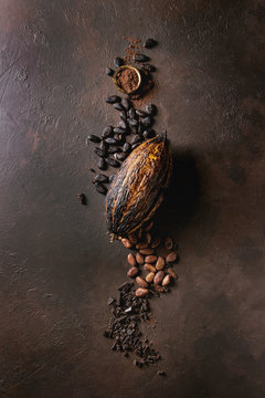 Variety of fresh and dry cocoa beans and cocoa pod with chopped dark chocolate and cocoa powder over brown texture background. Flat lay, space