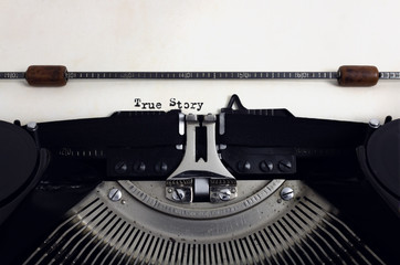 Old retro vintage black typewriter with close-up typing text True Story as heading on aged paper
