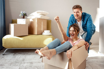 Young family couple bought or rented their first small apartment. Cheerful woman scream sitting in box. Guy move her. They play game during moving in.