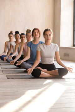 Group of attractive women practicing yoga in Sukhasana pose