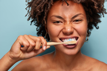 Dental hygiene concept. Self confident mixed race young woman brushes teeth with toothpaste and toothbrush, stands in front of mirror nude, isolated on blue background. Medicine, health care