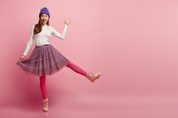 Full length shot of impressed lady has happy surprised expression, waves with hand, greets someone, stands on one legs, wears long skirt, boots, ready for winter, isolated over pink background