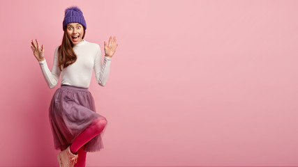 Indoor shot of impressed lady with shocked happy expression, pulls palms towards, raises knee, wears pink pantyhose, headgear, white jumper and skirt, reacts on positive news, stands indoor alone