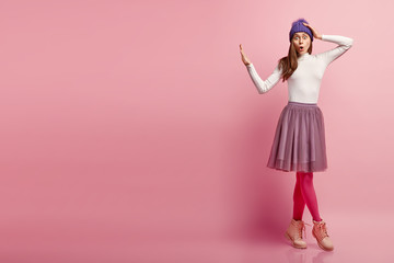 Stunned young hipster girl in fashionable outfit, opens mouth from shock, keeps hand aside in refusal gesture, asks not scare her, models over pink studio wall, empty space for your advertisement