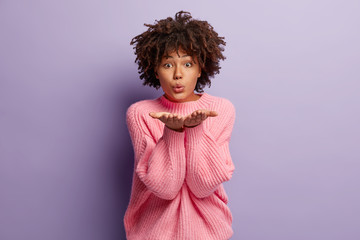 Photo of attractive young woman spreads hands near face, makes mwah to camera, dressed in oversized jumper, expresses love to beloved person, isolated over purple background. Flirting concept