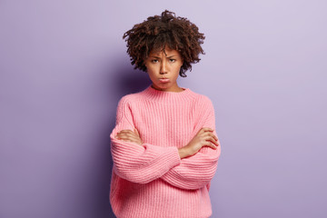 Upset dark skinned young lady has dejected facial expression, crosses hands over chest, offended for bad attitude, looks in dissatisfaction, wears pink sweater, isolated over purple background.