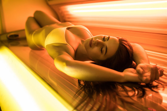 Beautiful young woman in sexy bikini have tanning skin treatment in modern solarium