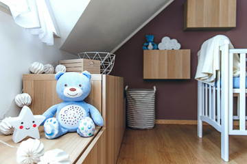 Stylish and cute scandinavian newborn baby room with toys, cotton lamps, teddy bears, baby cot and star. Modern interior with color background wall. Bright and sunny interior .