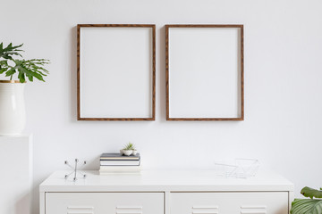 Stylish home interior with two brown wooden mock up photo frames on the white shelf with books, beautiful leaf, stand and home accessories. Minimalistic concept of white room decor.